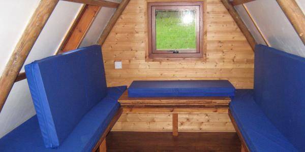 The seats inside an apex glamping pod convert into a sleeping area