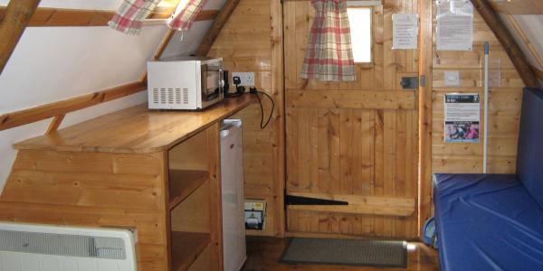 The kitchen area inside an apex glamping pod with a heater, fridge, kettle, toaster and microwave