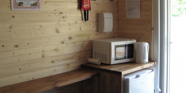 The kitchen area inside a glamping bothy with a heater, fridge, kettle, toaster and microwave