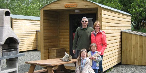 A family outside a glamping bothy with outside secure storage shed